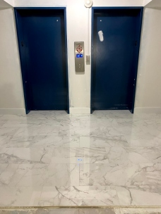 Personal elevators landing. Elevators doors in dark color on white wall. Mirrors on the side of the door will not be reinstalled.