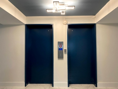 Lights of personal elevators landing. Ceiling painted with darker color.